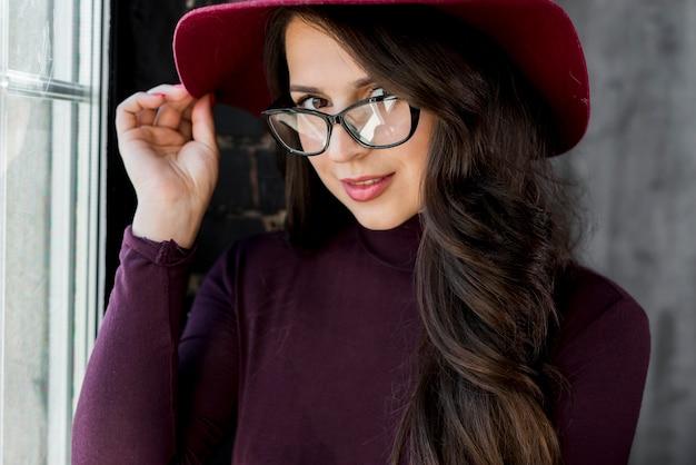 Jeune femme, lunettes, tenue, main, chapeau, dessus, tête Photo gratuit