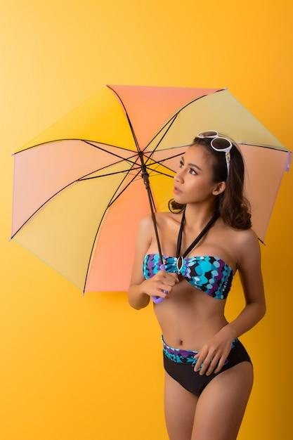Jeune femme en maillot de bain isolé sur jaune Photo gratuit