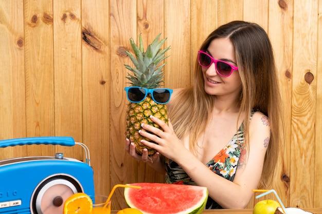 Jeune femme en maillot de bain tenant un ananas avec des lunettes de soleil Photo Premium