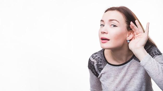 Jeune femme avec la main derrière l'oreille en écoutant de près Photo gratuit