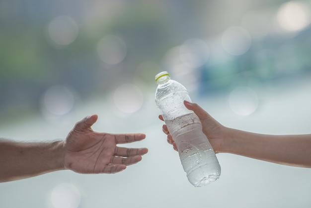 Jeune femme main donnant ou servant une bouteille d'eau potable fraîche à un homme après un exercice de fitness. Photo Premium