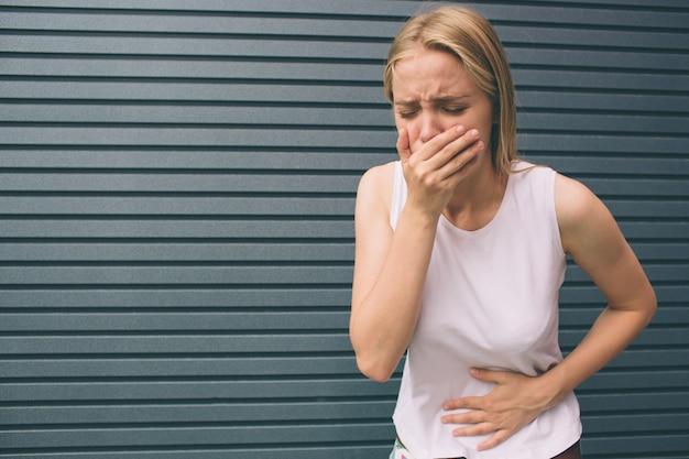 Jeune Femme Avec Les Mains Sur Le Ventre Ayant Une Douleur Douloureuse Mal Isolée Sur Gris. Intoxication Alimentaire, Grippe, Crampes. Problèmes De Santé. Photo Premium