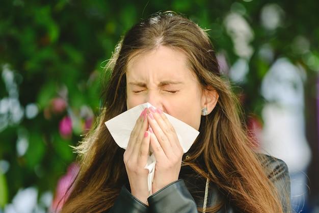 Jeune femme malade millénaire éternue tenant un mouchoir en tissu et soufflant en essuyant son nez qui coule Photo Premium