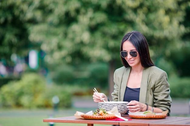 Jeune femme mangeant des nouilles à emporter dans la rue Photo Premium
