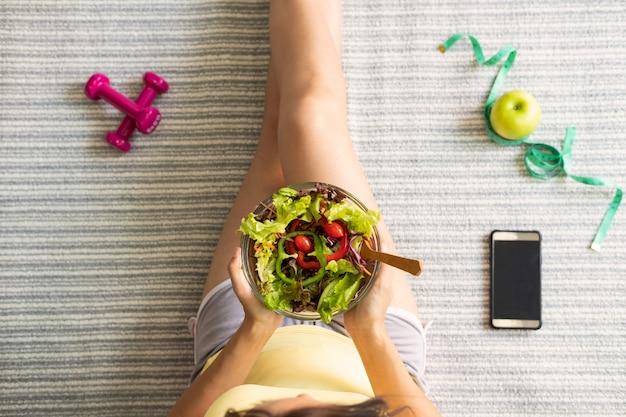 Jeune femme mangeant une salade maison à la maison, mode de vie sain, concept de régime Photo Premium