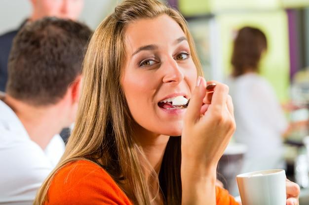 Jeune femme, manger, crème, à, café Photo Premium