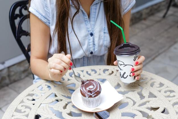 Jeune femme, manger, muffin, et, boire, café, dans, dehors, café, gros plan Photo Premium