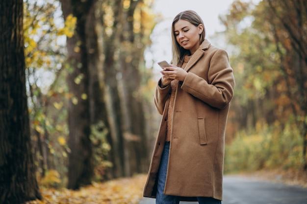 Jeune femme en manteau debout sur la route dans un parc en automne Photo gratuit