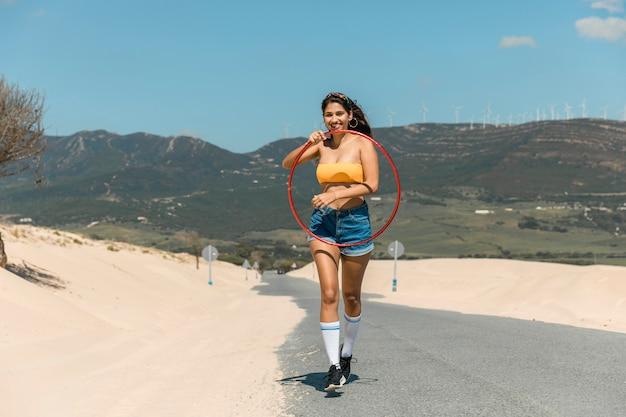 Jeune femme marchant avec cerceau sur le sable Photo gratuit