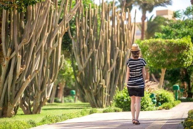 Jeune femme marchant à côté des cactus Photo gratuit