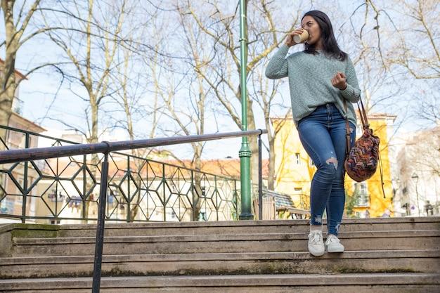 Jeune femme marchant dans les escaliers de la ville et buvant du café Photo gratuit