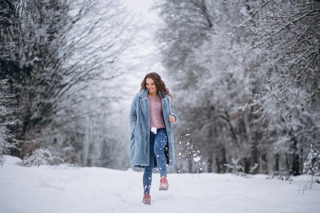 Jeune femme marchant dans un parc d'hiver Photo gratuit