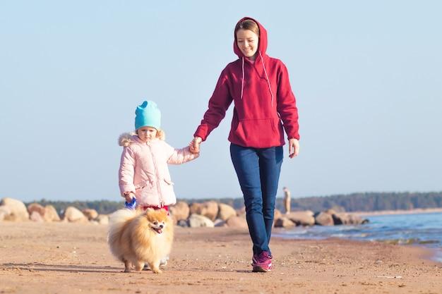Jeune Femme Marche Avec Fille Et Chien Sur La Plage. Photo Premium