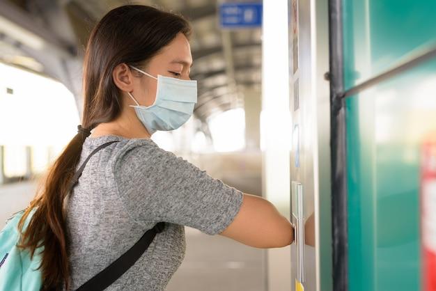 Jeune Femme Avec Masque En Appuyant Sur Le Bouton De L'ascenseur Avec Coude Pour Empêcher La Propagation Du Virus Corona à La Station De Skytrain Photo Premium