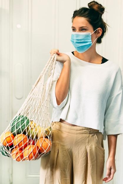 Une Jeune Femme Avec Un Masque Facial Et Un Sac à Provisions En Filet Réutilisable Plein De Fruits Et Légumes Photo Premium