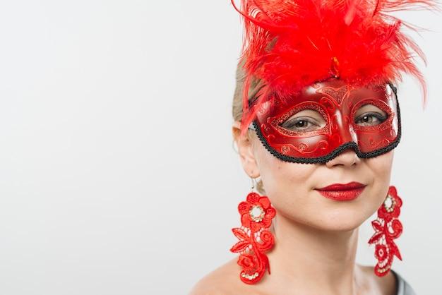 Jeune femme, masque, plumes rouges, boucles d'oreilles Photo gratuit