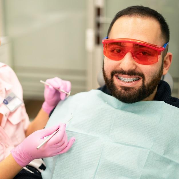 Jeune femme médecin dentiste et patient souriant à la caméra à la clinique dentaire Photo Premium