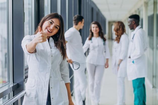 Jeune Femme Médecin Avec Le Geste Du Pouce En L'air, Debout Dans Le Couloir De L'hôpital Photo gratuit