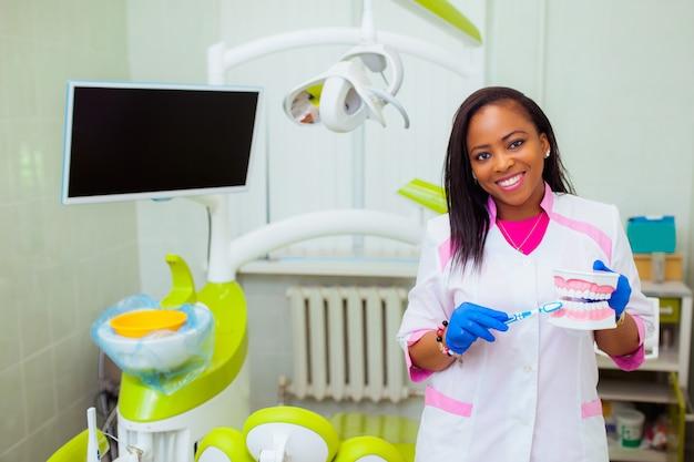 Jeune Femme Médecin Noir En Clinique Dentaire. Le Dentiste Est Debout Avec Un Mannequin Et Parle De Santé. Technologie Médicale Photo Premium