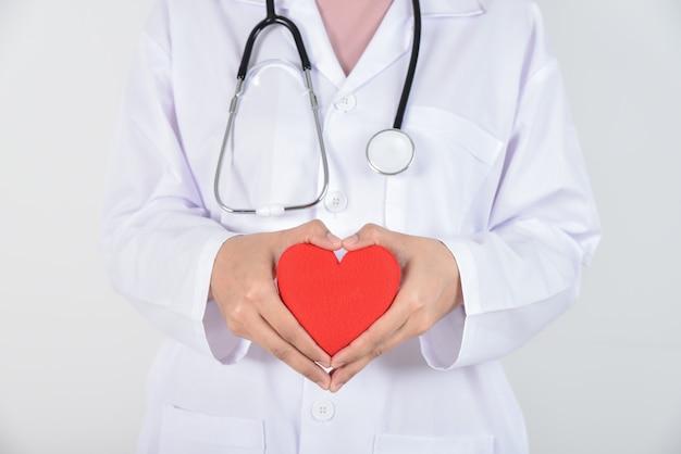 Jeune femme médecin avec stéthoscope tenant un coeur rouge dans ses mains sur blanc Photo Premium
