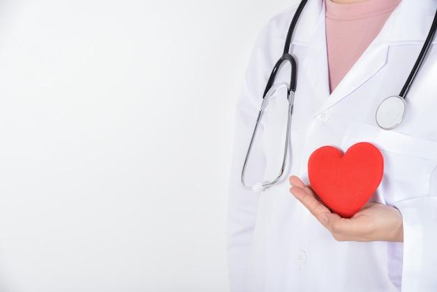 Jeune femme médecin avec stéthoscope tenant un coeur rouge à la main sur blanc Photo Premium