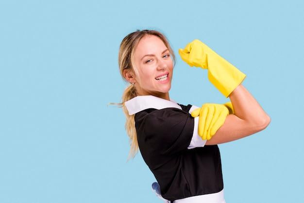 Jeune femme de ménage montrant son muscle contre le mur bleu Photo gratuit