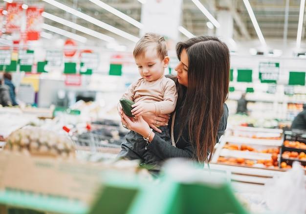 Jeune Femme Mère Avec Mignon Bébé Garçon Enfant En Bas âge Sur Les Mains Achète Le Freshavocado En Supermarché Photo Premium