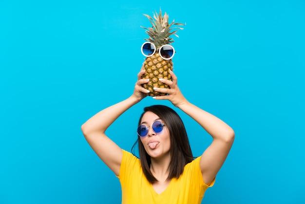 Jeune femme mexicaine sur un mur bleu isolé, tenant un ananas avec des lunettes de soleil Photo Premium