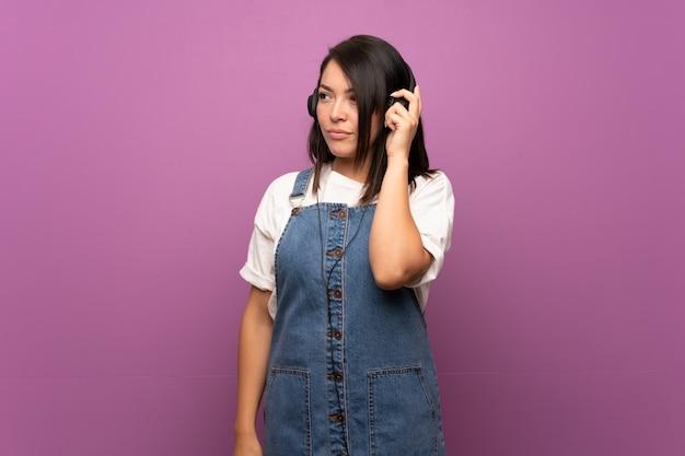 Jeune femme mexicaine sur mur isolé, écouter de la musique avec des écouteurs Photo Premium