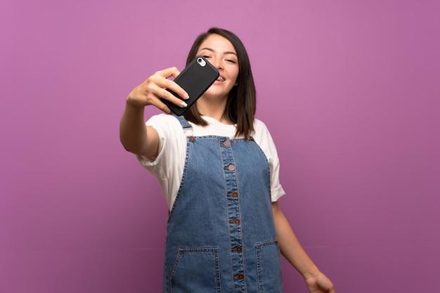 Jeune femme mexicaine sur mur isolé faisant selfie avec téléphone portable Photo Premium