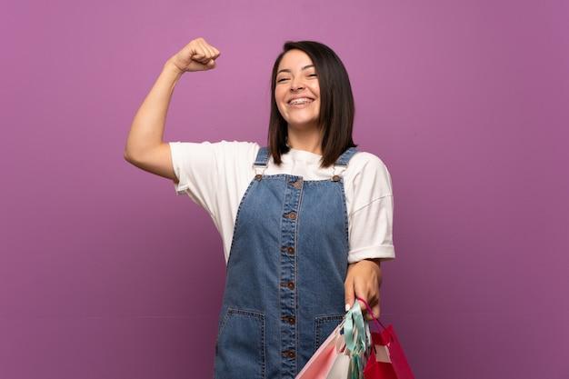Jeune femme mexicaine sur mur isolé tenant beaucoup de sacs à provisions Photo Premium
