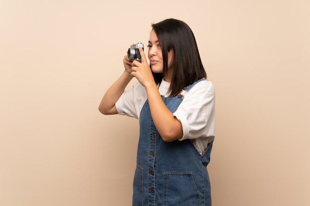 Jeune femme mexicaine sur mur isolé, tenant une caméra Photo Premium