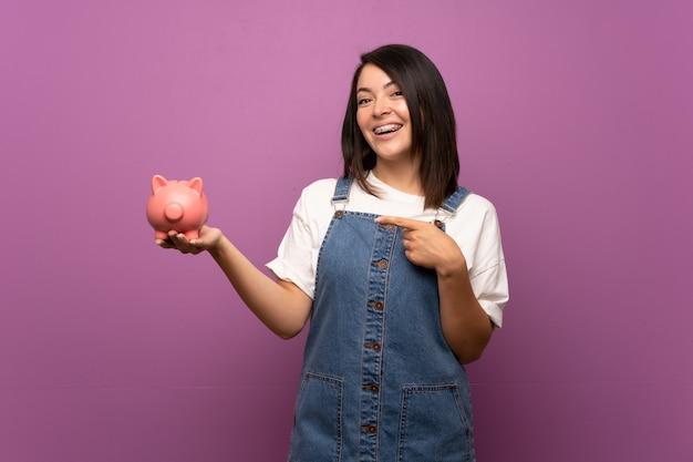 Jeune femme mexicaine sur mur isolé tenant une grande tirelire Photo Premium