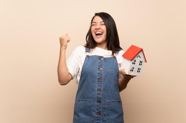 Jeune femme mexicaine sur mur isolé tenant une petite maison Photo Premium