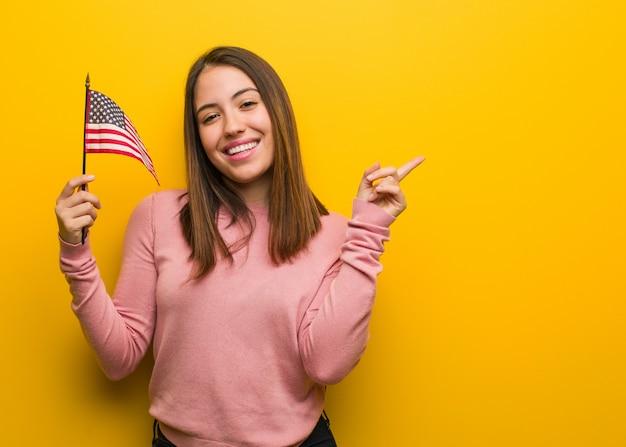 Jeune femme mignonne tenant un drapeau des états-unis pointant vers le côté avec le doigt Photo Premium