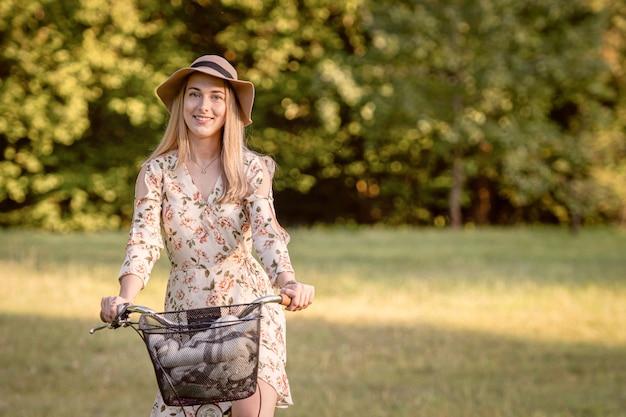 Jeune Femme Mince Et Blonde à Vélo Contre Le Paysage Du Parc Défocalisé. Nuance De Couleur D'automne. Photo Premium
