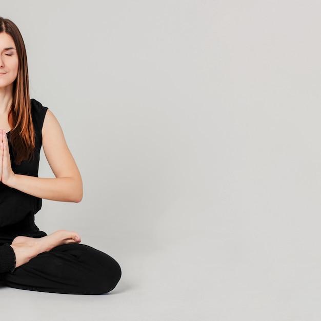 Jeune femme mince brune en noir assis en position du lotus au yoga isolé Photo Premium