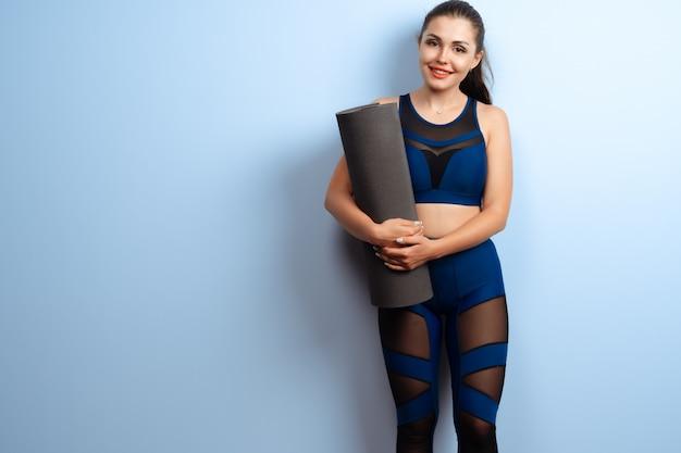 Jeune femme mince, tenant des tapis de yoga dans ses mains Photo Premium
