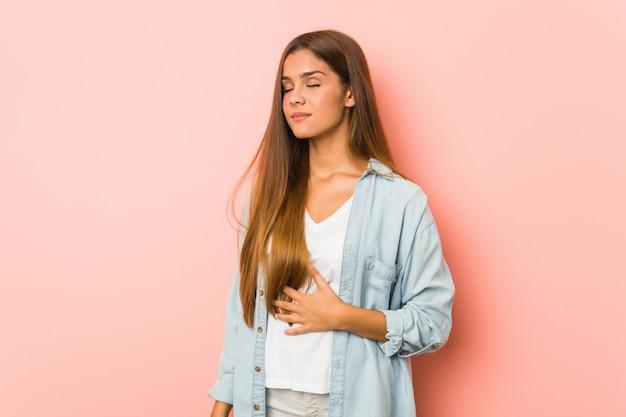 Jeune femme mince touche le ventre, sourit doucement, concept de restauration et de satisfaction. Photo Premium