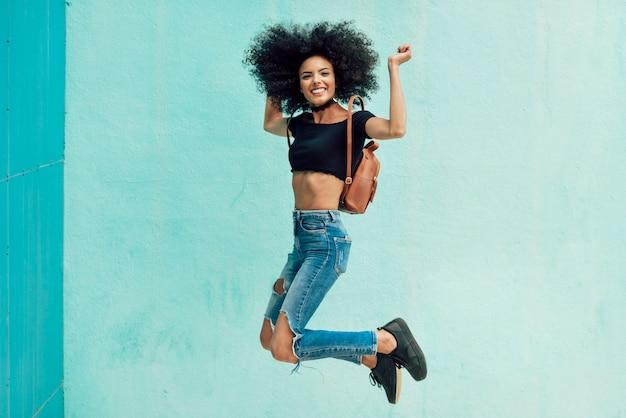 Jeune femme mixte aux cheveux afro, sauter à l'extérieur. Photo Premium