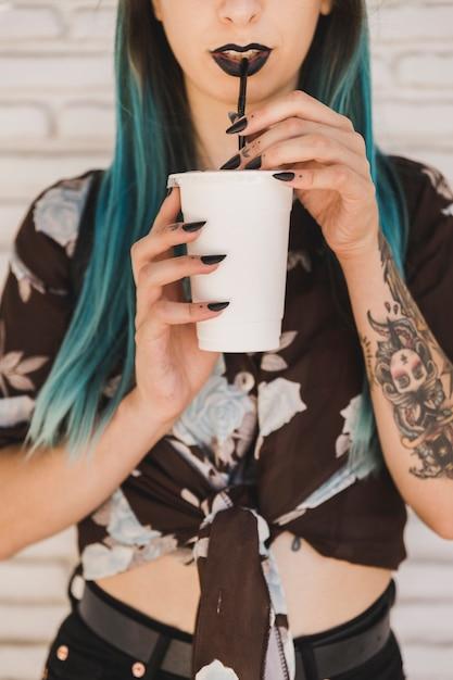 Jeune femme moderne, boire du café avec de la paille Photo gratuit