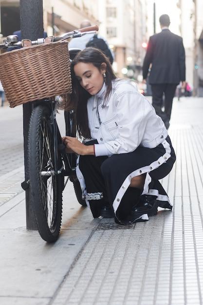 Jeune femme moderne en regardant son vélo dans la rue Photo gratuit