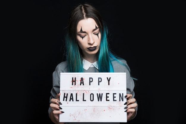 Jeune femme montrant l'inscription happy halloween Photo gratuit