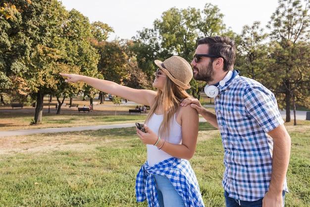 Jeune femme montrant quelque chose à son petit ami à l'extérieur Photo gratuit
