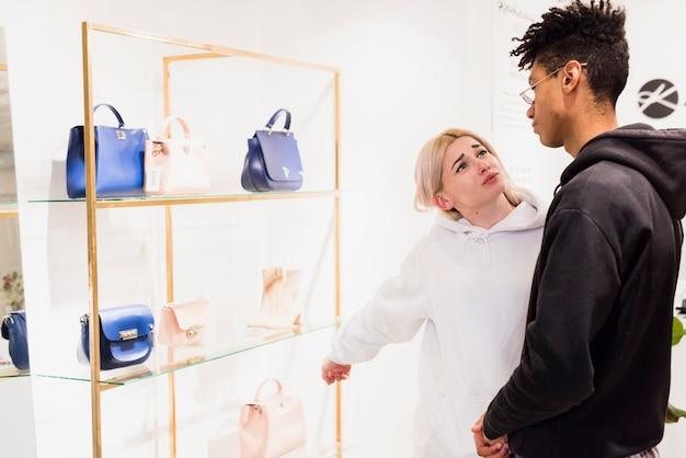 Jeune femme montrant un sac à main sur une étagère, elle veut acheter son petit ami Photo gratuit