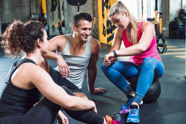 Jeune femme montre montre au poignet à ses amis dans la salle de gym Photo gratuit
