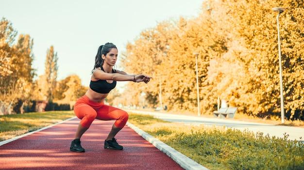 Jeune femme motivée faisant des squats dans le parc en plein air. Photo Premium