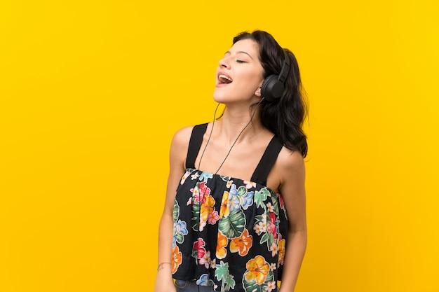 Jeune femme sur un mur jaune isolé, écouter de la musique avec des écouteurs Photo Premium
