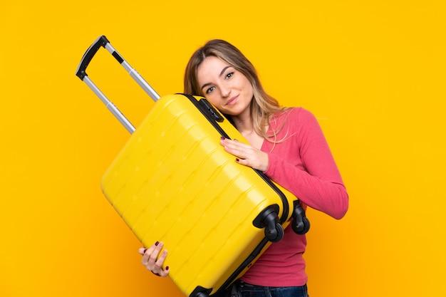 Jeune Femme Sur Un Mur Jaune Isolé En Vacances Avec Valise De Voyage Photo Premium