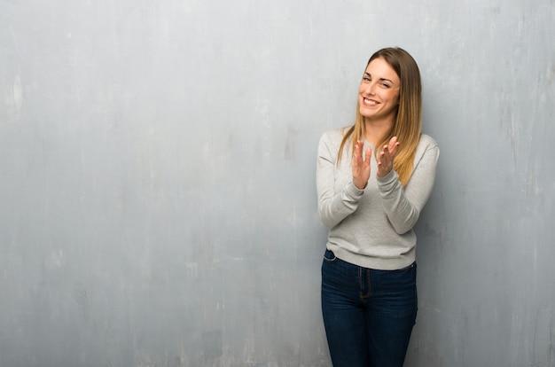 Jeune femme sur un mur texturé applaudissant après une conférence Photo Premium